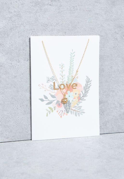 """عقد مع بطاقة هدايا تحمل عبارة """"LOVE"""""""